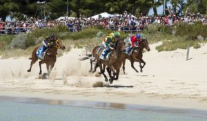 Horses race along Rockingham beach